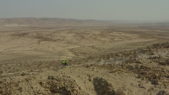 aerial panning shot of biker moving downhill on track against clear sky, drone flying over desert - negev, israel - middle east stock videos & royalty-free footage