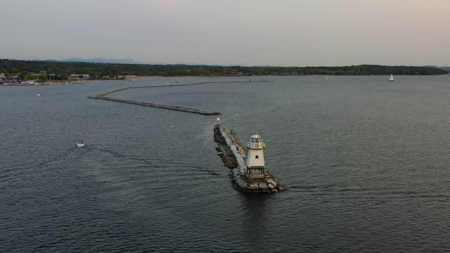 aerial panning shot of boat moving by lighthouse on lake against sky, drone flying over groyne near city at sunset - burlington, vermont - vermont stock videos & royalty-free footage