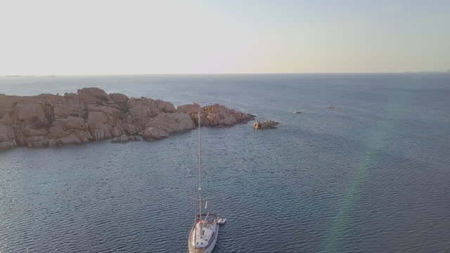 stockvideo's en b-roll-footage met aerial panning shot of boat moving in ocean on sunny day, drone flying over famous landmark against sky - corsica, france - sunny