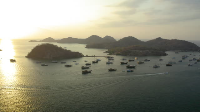 aerial panning shot of boats moored on sea by islands against sky, drone flying over ocean during sunset - komodo island, indonesia - komodo island stock videos & royalty-free footage