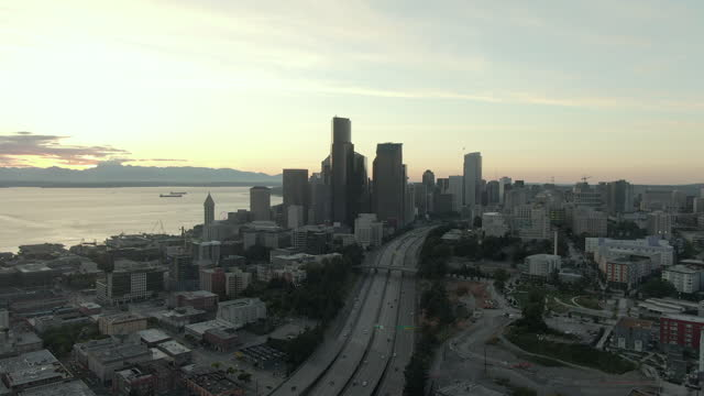 aerial panning shot of buildings by dr jose p rizal bridge in city, drone flying backward over modern downtown by elliott bay against sky at sunset - seattle, washington - elliott bay stock videos & royalty-free footage