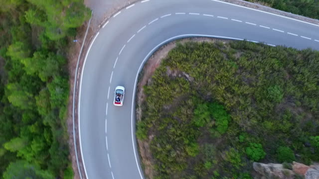 aerial panning shot of car on road amidst green trees and plants, drone flying over natural landscape - montserrat, spain - winding road stock videos & royalty-free footage