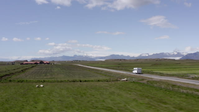 aerial panning shot of caravan moving on road amidst green landscape against sky - southwestern iceland, iceland - iceland stock videos & royalty-free footage