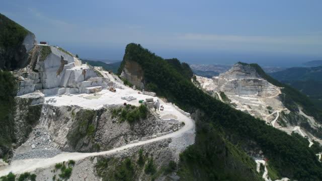 aerial panning shot of carrara marble quarry, tuscany, italy - cava video stock e b–roll