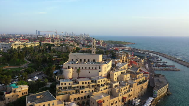 aerial panning shot of church amidst buildings in city near sea, drone flying over cityscape against sky during sunset - jaffa, israel - jaffa stock videos & royalty-free footage