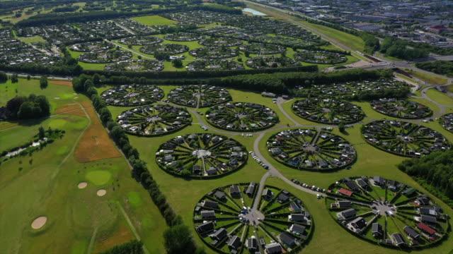 vídeos de stock, filmes e b-roll de aerial panning shot of circular suburb in town on sunny day, drone flying over townscape - copenhagen, denmark - dinamarca