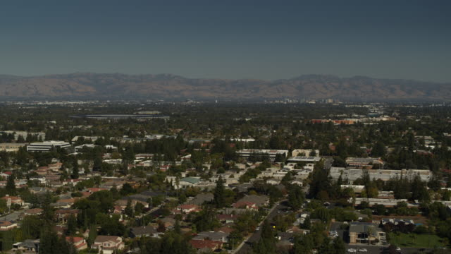 aerial panning shot of cityscape near mountain range / cupertino, california, united states - silicon valley stock videos & royalty-free footage