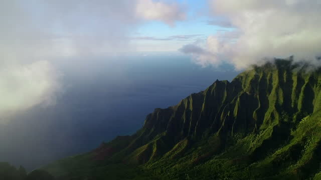 aerial panning shot of clouds moving over mountain peak, drone flying over famous island by sea during sunset - kauai, hawaii - 4k stock videos & royalty-free footage