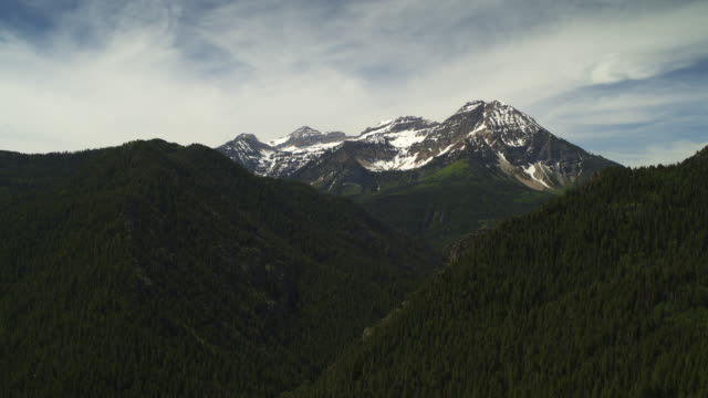 aerial panning shot of clouds over trees in mountain range / american fork canyon, utah, united states - american fork canyon stock videos & royalty-free footage