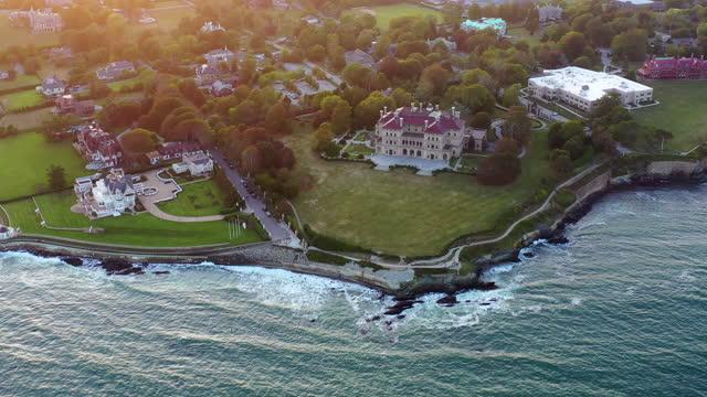 vídeos de stock e filmes b-roll de aerial panning shot of coastal city by waves splashing on sea at sunset, drone flying forward over coastline - newport, rhode island - rhode island