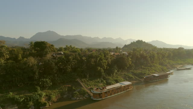 aerial panning shot of cruise ships moored at riverbank, drone is flying left to right over water - luang prabang, laos - cruise stock videos & royalty-free footage