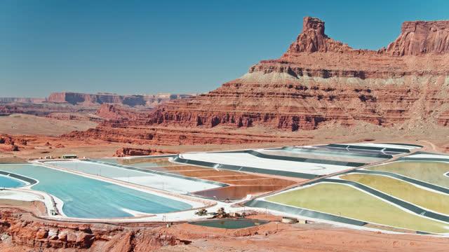 aerial panning shot of evaporation ponds at potash mine near moab, utah - moab utah stock videos & royalty-free footage