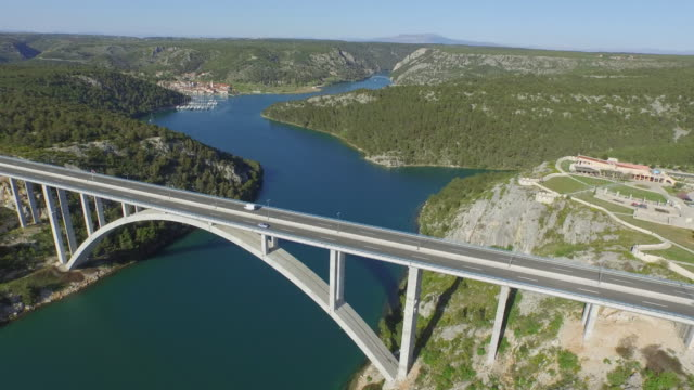 aerial panning shot of famous arch bridge over river on sunny day, drone flying over vehicles on road against sky - heart island, croatia - arch bridge stock videos & royalty-free footage