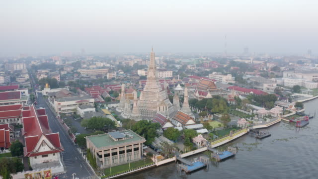 aerial panning shot of famous buddhist temple by river against sky, drone flying from famous landmark in city at sunset - bangkok, thailand - bangkok video stock e b–roll