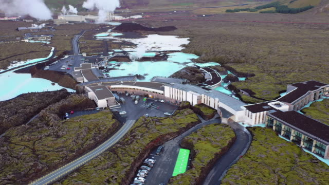 aerial panning shot of famous geothermal spa with buildings on landscape, drone flying over lagoon amidst rock formation - blue lagoon, iceland - 健康スパ点の映像素材/bロール