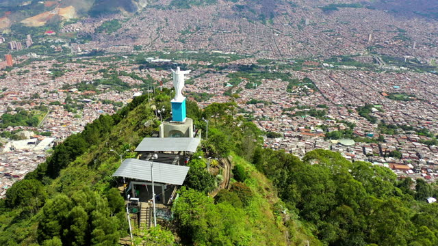 aerial panning shot of famous monument on mountain in city, drone flying over popular landscape on sunny day - medellin, colombia - religion stock-videos und b-roll-filmmaterial