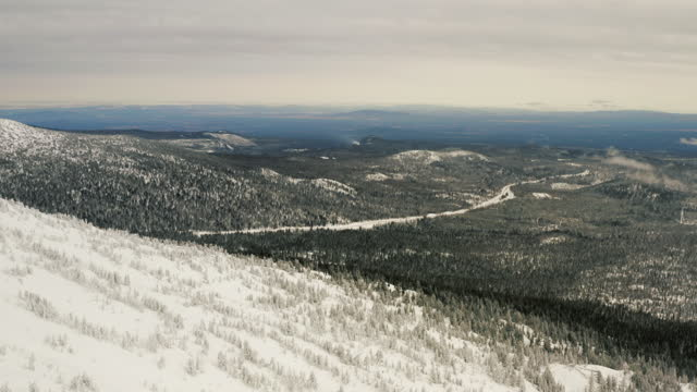 aerial panning shot of forest over snowy mountain, drone flying over mt bacholer against cloudy sky - bend, oregon - アメリカ太平洋岸北西部点の映像素材/bロール