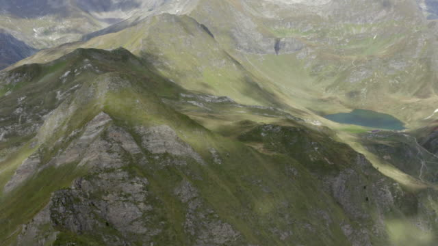 aerial panning shot of glacial lakes amidst green mountains on sunny day, drone flying over natural landscape - swiss alps, switzerland - moos stock-videos und b-roll-filmmaterial