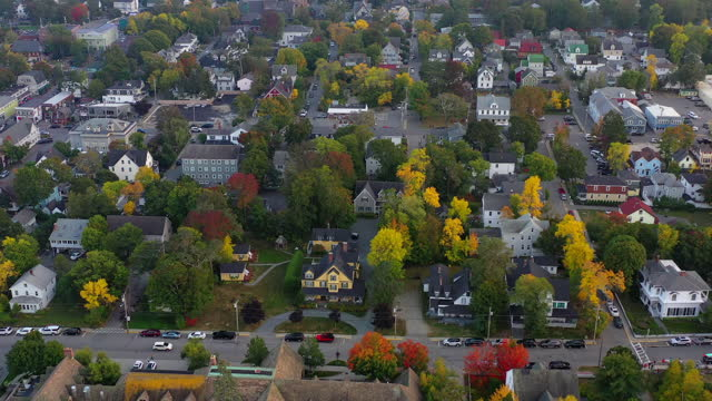 aerial panning shot of houses and trees with vehicles on streets in city, drone flying over residential district - bar harbor, maine - aerial stock videos & royalty-free footage