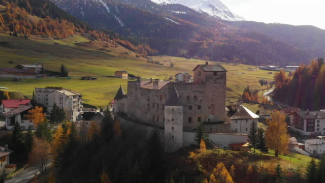 aerial: panning shot of houses in small city by mountains during sunny day, landscape during autumn - nauders, austria - castle stock videos & royalty-free footage