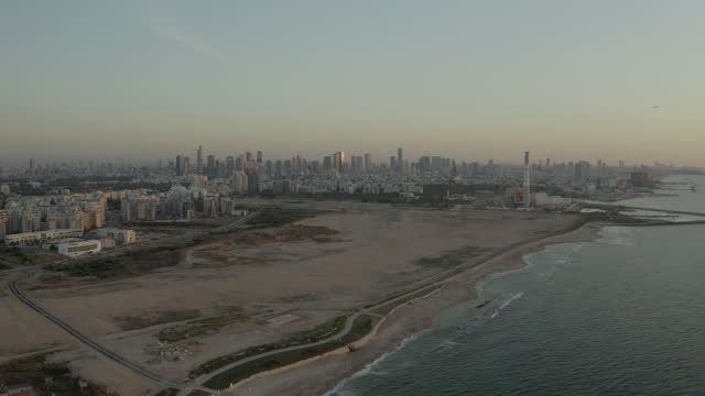 aerial panning shot of idyllic view of beach by road during sunset, drone flying over buildings against clear sky - tel aviv, israel - scenics stock videos & royalty-free footage