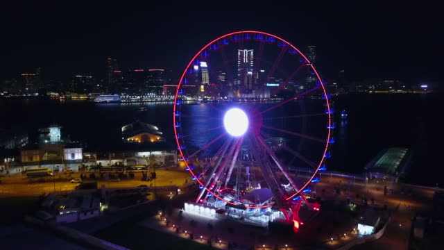 aerial panning shot of illuminated ferris wheel by sea in city at night, drone flying near modern buildings - hong kong, china - big wheel stock-videos und b-roll-filmmaterial