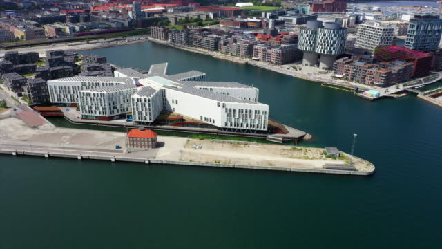 vídeos de stock e filmes b-roll de aerial panning shot of modern building in city by sea on sunny day, drone flying over water - copenhagen, denmark - embarcação comercial