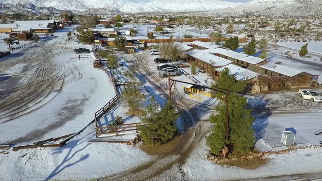 aerial panning shot of motel signboard over tire tracks on snow in town, drone flying near structures against snowcapped mountains on sunny day - joshua tree, california - placard stock videos & royalty-free footage