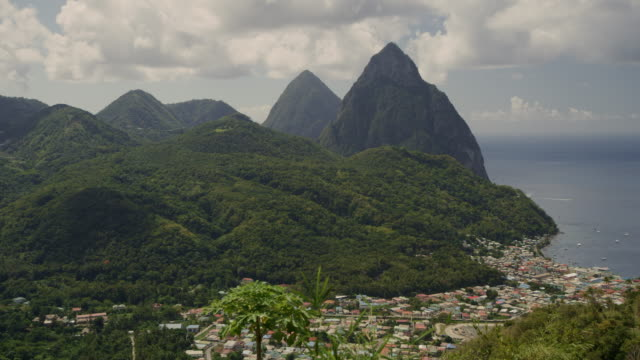 aerial panning shot of mountains and distant houses at waterfront / st. lucia - st. lucia stock videos & royalty-free footage