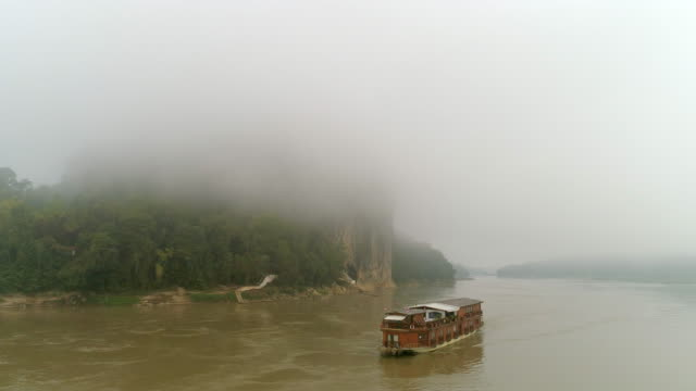 vídeos de stock e filmes b-roll de aerial panning shot of nautical vessel moving in river against sky, drone flying over water during foggy weather - mekong river, laos - cruzeiro