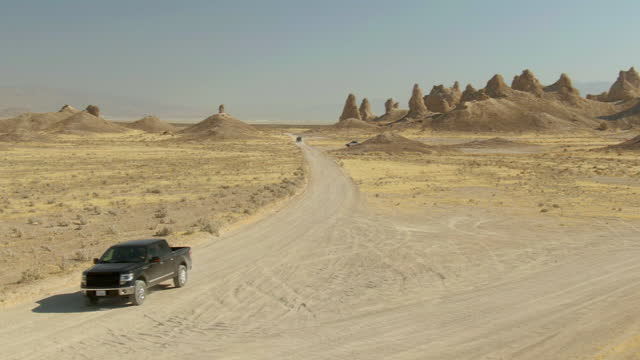 aerial panning shot of off-road vehicle at semi-arid desert against sky, drone flying over trona pinnacles - pinnacle stock videos & royalty-free footage