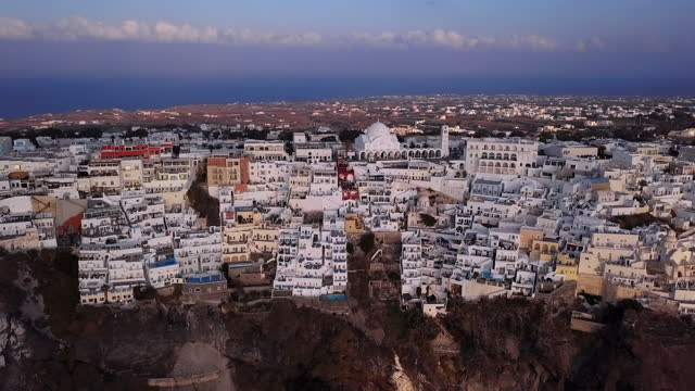 aerial panning shot of orthodox metropolitan cathedral in city, drone flying forward towards structures on mountain at sunset - santorini, greece - cyclades islands stock videos & royalty-free footage