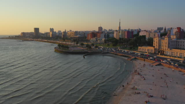 aerial panning shot of people at beach in city against sky during sunset, drone flying over shore by vehicles on street - montevideo, uruguay - montevideo stock-videos und b-roll-filmmaterial