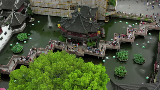 aerial panning shot of people at traditional building complex with pond, drone flying over tourists in city - shanghai, china - bamboo plant stock videos & royalty-free footage