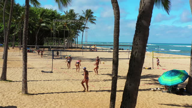 aerial: panning shot of people playing volleyball at beach during vacation on sunny day - oahu, hawaii - 海岸線点の映像素材/bロール