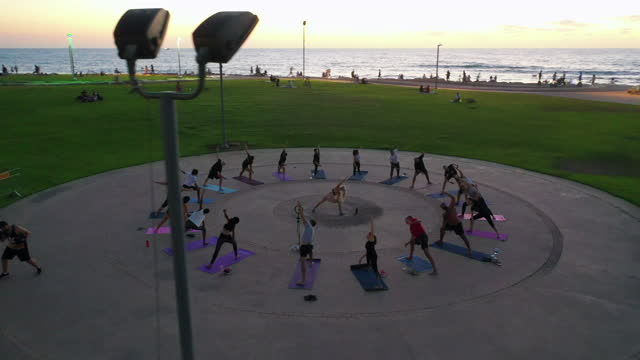 aerial panning shot of people practicing yoga at park during dusk, drone flying over instructor and students in city - tel aviv, israel - healthy lifestyle stock videos & royalty-free footage