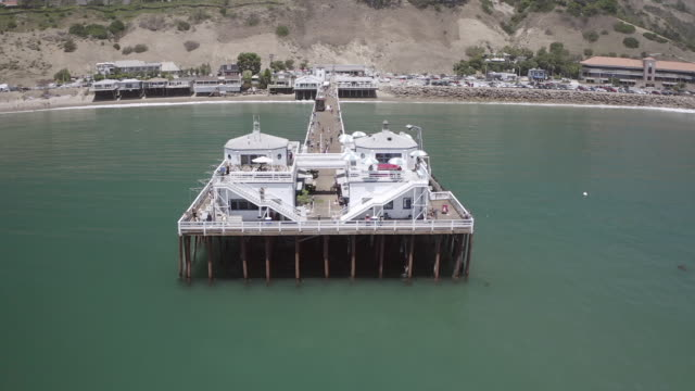 aerial panning shot of pier over ocean in city during vacation, drone moving over sea - malibu, california - malibu stock videos & royalty-free footage