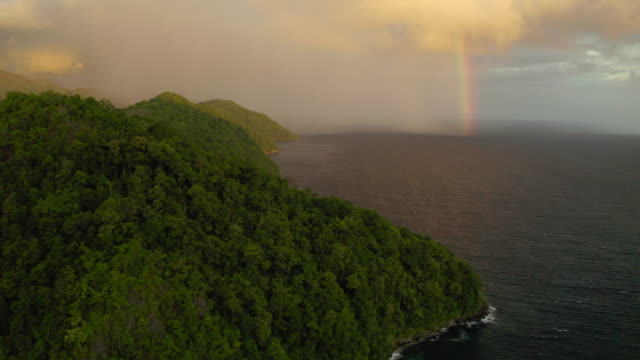 aerial panning shot of rainbow over sea near green mountains against sky, drone flying over landscape during sunset - wakatobi regency, indonesia - rainforest stock videos & royalty-free footage