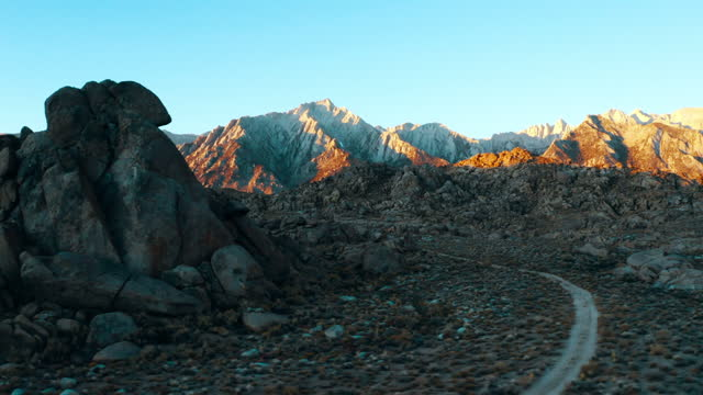 aerial panning shot of rocks at famous natural landmark against blue sky, drone flying near rocky mountains on sunny day - alabama hills, california - natural landmark stock videos & royalty-free footage