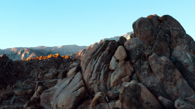 aerial panning shot of rocks at famous natural landmark against sky, drone flying near rocky mountains on sunny day - alabama hills, california - natural landmark stock videos & royalty-free footage
