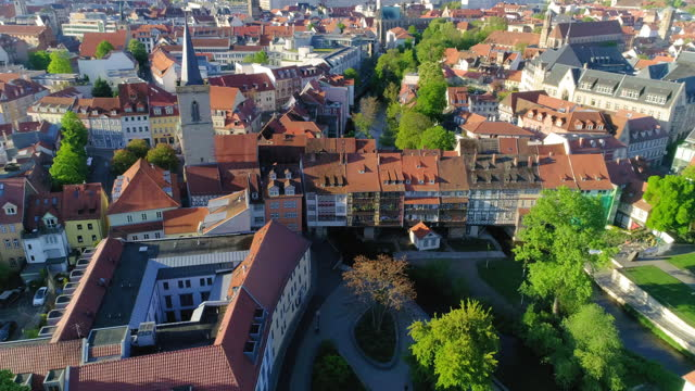 aerial panning shot of roofed houses over landscape in city on sunny day - erfurt, germany - sunny点の映像素材/bロール