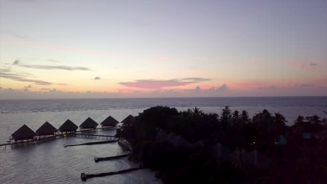 aerial panning shot of silhouette resort against sky at sunset, drone ascending over sea with luxurious water bungalows - vaadhoo, maldives - hotel stock videos & royalty-free footage