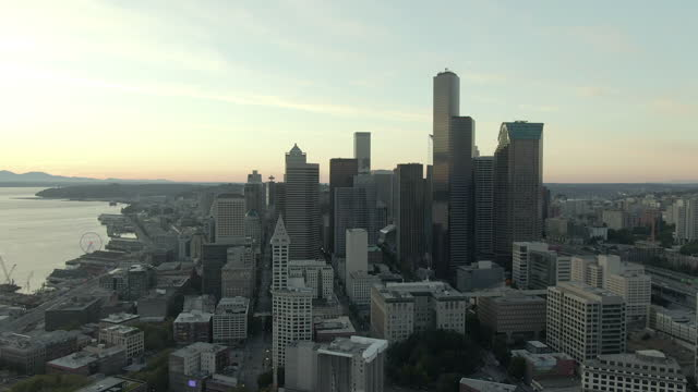 aerial panning shot of skyscrapers in downtown by dr jose p rizal bridge, drone flying over modern city by elliott bay against sky at sunset - seattle, washington - elliott bay stock videos & royalty-free footage