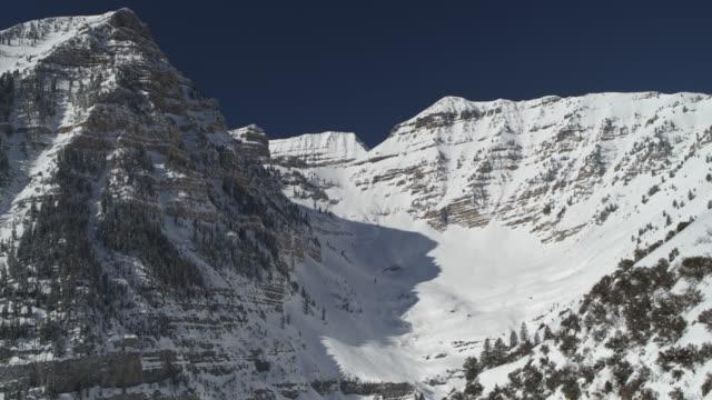 aerial panning shot of snow covered mountain range / aspen grove, utah, united states - ロッキー山脈点の映像素材/bロール