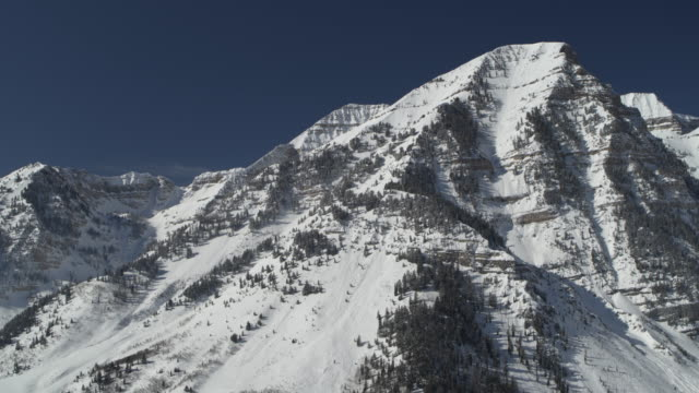 aerial panning shot of snow covered mountain range / aspen grove, utah, united states - rocky mountains stock videos & royalty-free footage