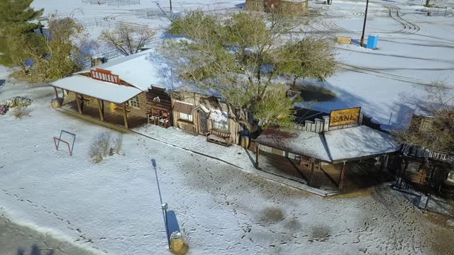 aerial panning shot of snow covered wooden roof in town on sunny day, drone flying over footprints during winter - joshua tree, california - joshua tree national park stock videos & royalty-free footage
