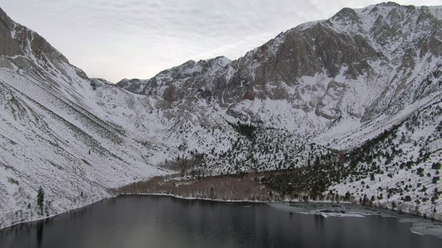 aerial panning shot of snowcapped mountain range by convict lake, drone flying forward over white landscape during winter - mammoth lakes, california - mammoth lakes video stock e b–roll