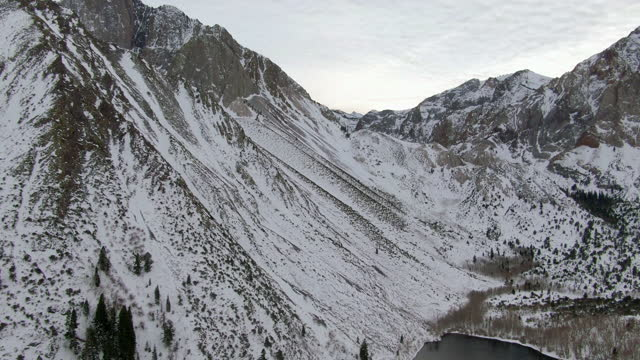 aerial panning shot of snowcapped mountains by convict lake against sky, drone flying forward over white landscape during winter - mammoth lakes, california - californian sierra nevada stock videos & royalty-free footage