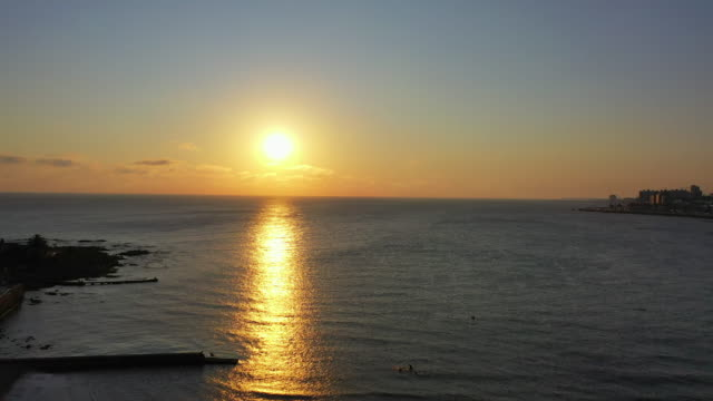 aerial panning shot of sun with reflection on sea against sky at sunset, drone flying over promenade in city - montevideo, uruguay - montevideo stock-videos und b-roll-filmmaterial