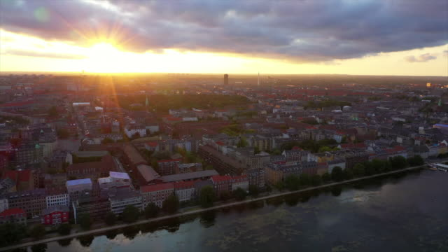 aerial panning shot of sunbeam over cityscape with lake during sunset, drone flying over city against sky - copenhagen, denmark - copenhagen stock videos & royalty-free footage